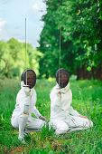 picture of rapier  - Two fencers women squatting down with rapiers pointing up ready for competition - JPG