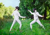image of rapier  - Two rapier fencer women fighting over beautiful nature background - JPG