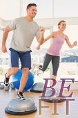 stock photo of step aerobics  - Couple doing step aerobics in fitness studio against be fit - JPG