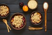 picture of crisps  - Overhead shot of rustic bowls filled with baked plum and nectarine crumble or crisp photographed on dark wood with natural light - JPG