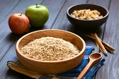 stock photo of oats  - Raw rolled oats in wooden bowl with apples cinnamon sticks and a bowl of fruit crumble in the back photographed on dark wood with natural light  - JPG