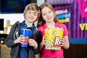 pic of brother sister  - Portrait of happy brother and sister holding snacks against cinema concession stand - JPG
