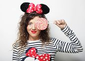 stock photo of lolita  - young happy curly woman with mouse ears holding lollipop - JPG