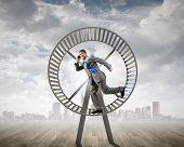 pic of hamster  - Young businessman running in huge hamster wheel - JPG