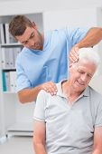 pic of physical therapist  - Physical therapist giving massage to senior male patient in clinic - JPG