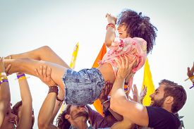 stock photo of gathering  - Happy hipster woman crowd surfing at a music festival - JPG
