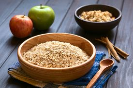 picture of oats  - Raw rolled oats in wooden bowl with apples cinnamon sticks and a bowl of fruit crumble in the back photographed on dark wood with natural light  - JPG