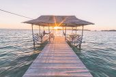 stock photo of marsala  - Tourist sitting on wooden jetty while watching a stunning sunrise on the sea from tourist resort - JPG