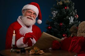 stock photo of letters to santa claus  - Happy Santa Claus writing a letter at the table - JPG