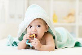 image of teething baby  - baby with teether in mouth under bathing towel at nursery - JPG
