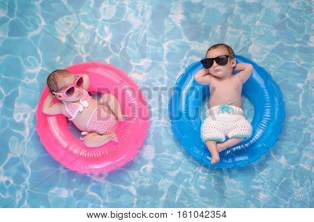 poster of Two month old twin baby sister and brother sleeping on tiny inflatable pink and blue swim rings. They are wearing crocheted swimsuits and sunglasses.