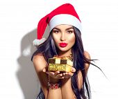 Beauty Christmas fashion model girl holding Xmas gift box. Beautiful lady, Long straight flying hair poster