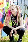 jovem mulher sentada no muro de graffitti