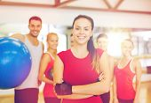fitness, sport, training, gym and lifestyle concept - smiling woman standing in front of the group o poster