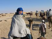 stock photo of yashmak  - Tourists in desert Sahara on camels in yashmak - JPG