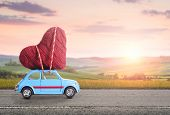 Blue retro toy car delivering heart for Valentines day against blurred rural Tuscany sunset landsca poster