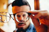 Closeup Portrait Of Young Man With Glasses, Who Has Eyesight Problems poster