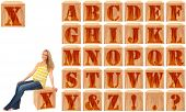 Wood engraved and stained alphabet blocks.  Featuring pregnant woman on Letter X.