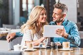Affectionate Couple Using Tablet At Table In Cafe And Looking At Each Other poster