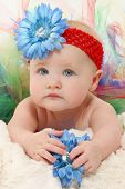 Adorable 5 month old baby girl in colorful tutu and flower hat close up.