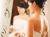 Closeup wedding shot of a slim beautiful woman wearing luxurious wedding dress standing opposite to