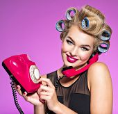 Young girl dials a phone number on an old phone. Young happy woman with blue curlers calling by retr poster