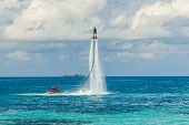 Silhouette Of A Fly Board Rider At Sea. Professional Rider Do Tricks In The Blue Lagoon. Tropical Wa poster