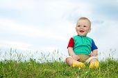 little baby sit on green grass under sky