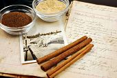 Collage of a vintage handwritten cookbook with cinnamon sticks, ginger, nutmeg, and an old photograp