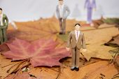 Small People Figures On Autumn Maple Leaves. Abstract Photo Of Autumn poster