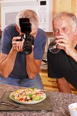 Senior male photographer taking food photos with friends