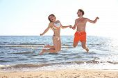 Happy Young Couple In Beachwear Jumping On Seashore poster