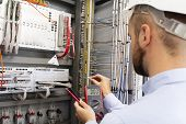 Engineer Electrician With Multimeter In Electrical Control Box Tests Equipment. Maintenance Of Elect poster