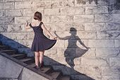 Young Beautiful Brunette Girl In Blue Dress Dancing With Her Shadow On Stone Wall Background, Concep poster