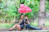 young couple with red balloons on natural background