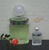 Fragrance For Ladies, Large Perfume Bottle Next To A Commercial Perfume Bottle In Front Of The Satin poster