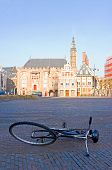The empty town square, early morning, with an abandoned bicycle and the sun-lit town hall in the background