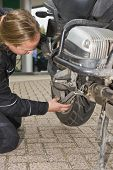 A motorist checking the rear suspension of his motorcycle