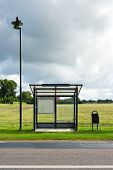A bus stop is depicted standing in front of a field. Dark clouds indicate a storm is coming. There i