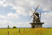 An old windmill is shown in a rural area. There are no people viewable. Horizontally framed shot.