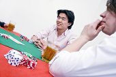 An Asian man sitting at the poker table during a game, ambiguously smiling at the competition