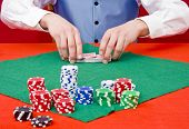 A dealer shuffling cards at a poker table with selective focus on the dealer's hands
