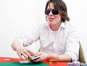 A player with big sunglasses displaying an ambiguous smile as part of his poker face