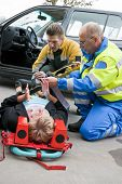 Multi-disciplinary medical team with a fireman and a paramedic, kneeling around a stretcher, and str