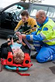 Paramedic and firefighting providing first aid to an injured woman on a stretcher