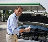 Man checking the oil levels in his car at a gas station, using a dipstick
