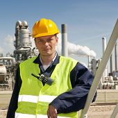 Portrait of an engineer in front of a petrochemical industry, with fire retardant clothing and a CB-