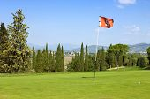The lush, manicured green at the ninth hole of a luxurious golf course in Tuscany, Italy