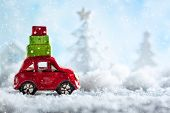 Red toy car carrying Christmas gifts in snowy landscape. Christmas concept with copy space. poster