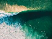 Aerial View Of Crashing Wave In Ocean With Surfers And Sunset Light. Wave Crashing On Reef. Top View poster